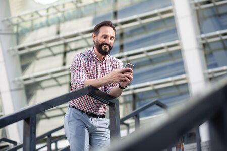 Joyful bearded man using his mobile phone outdoors
