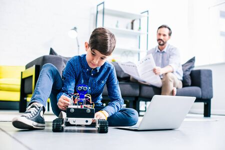 Enthusiastic smart boy playing with robotic device