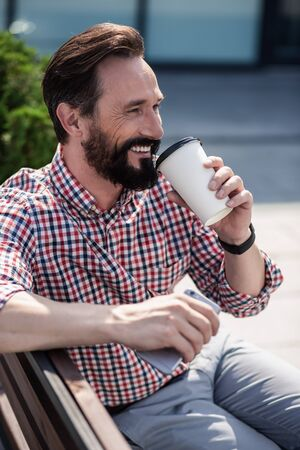 Overjoyed bearded man drinking coffee on the bench