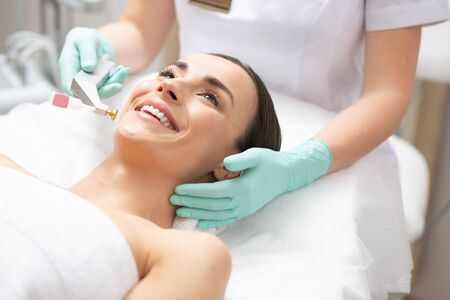 Face of happy lady and dermatologist holding metal tool