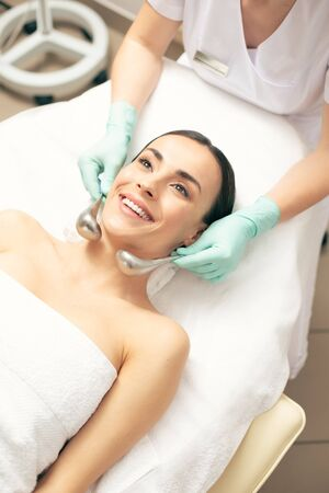 Top view of the cryo-sticks massage of smiling woman