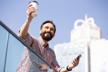 Joyful handsome man dringking tasty coffee outdoors Zdjęcie Seryjne