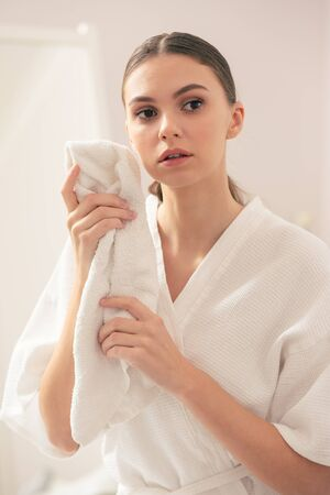 Waist up of serious woman standing and holding soft towel
