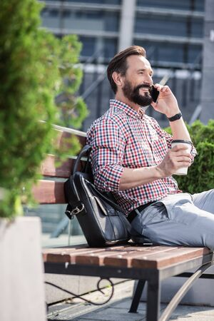 Happy bearded man resting on the bench with cup of coffee Stockfoto - 134869634