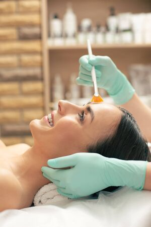 Face of excited woman lying and having her face cleaned Stock Photo
