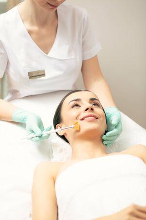 Smiling young woman enjoying peeling procedure in the clinic