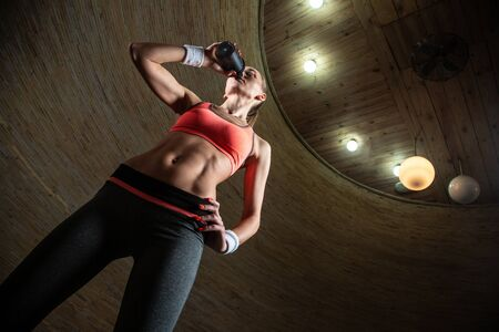Waist up of attractive slim lady drinking water from sporty bottle