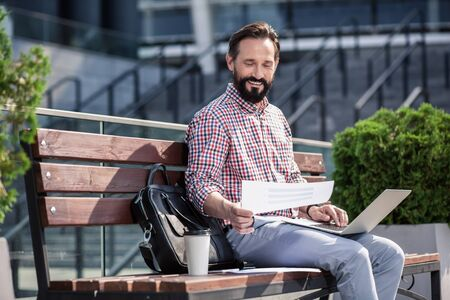 Positive male freelance worker sitting on the bench Stockfoto - 134869732