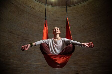 Relaxed woman in hammock meditating with closed eyes Standard-Bild