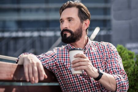Confident bearded man drinking tasty coffee outdoors