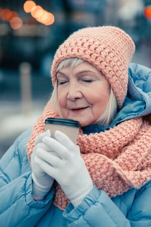 Pensioner closing her eyes while smelling coffee in the cup