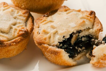 Broken off piece of mince pie with blueberry jam filling
