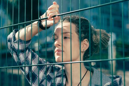 Laconic portrait of young lady leaning on the chain link fence