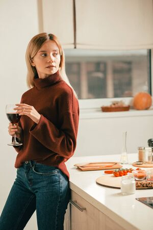 Beautiful thoughtful woman standing in the kitchen with wine