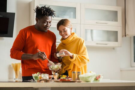 Peaceful couple smiling and adding salt to their salad Stockfoto