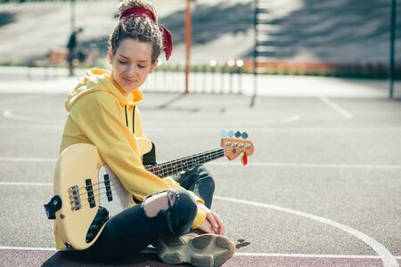 Calm lady turning her head while sitting on the ground with her guitar