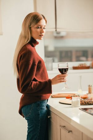 Attractive long haired lady thoughtfully holding glass of wine
