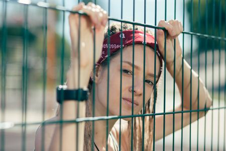 Close up of serious woman looking through the chain link fence