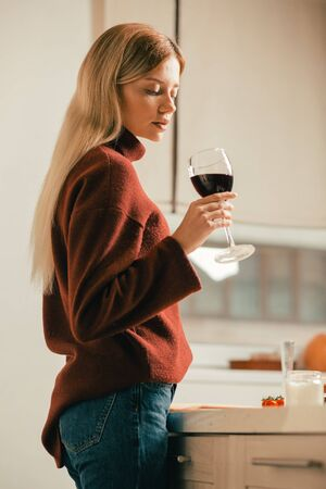 Beautiful lady looking attentively at wine in the glass