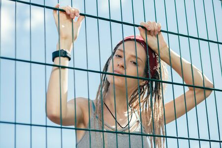 Peaceful tired lady leaning on the chain link fence and looking at you 版權商用圖片