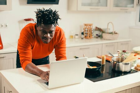 Attentive young man using modern laptop in the kitchen