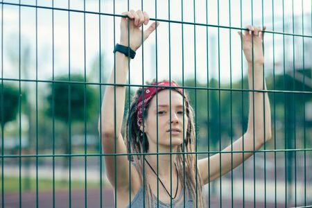 Beautiful lady putting both hands on the chain link fence and looking calm