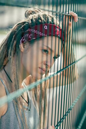 Portrait of frowning young lady leaning to the chain link fence 版權商用圖片