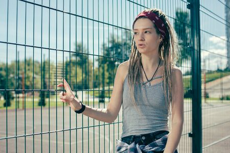 Serious lady with dreadlocks looking at the sports ground and thinking