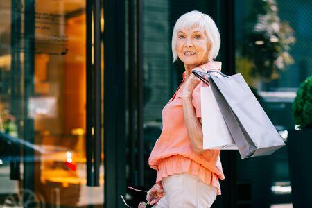 Happy pensioner in front of the shop doors