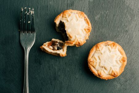 Metal fork lying near two mince pies on black surface Stock fotó