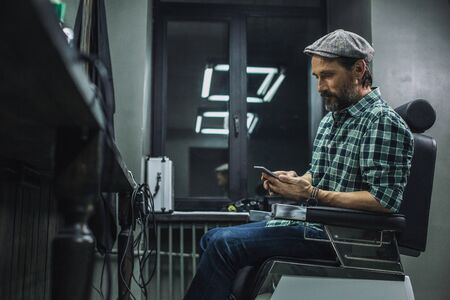 Waist up of calm man in flat hat sitting in barber shop