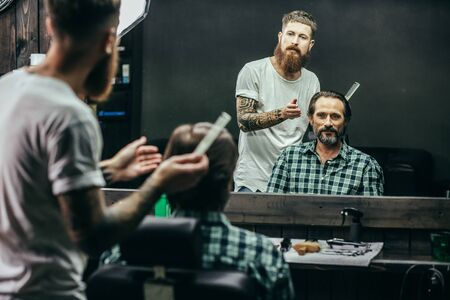 Handsome man looking at his reflection while the barber thinking