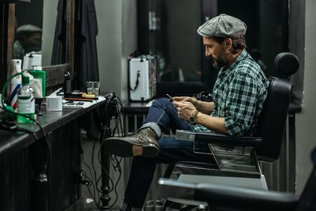 Calm man crossing legs while sitting with smartphone in barbershop