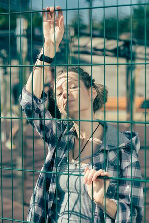 Beautiful lady standing on the sports ground and touching the chain link fence