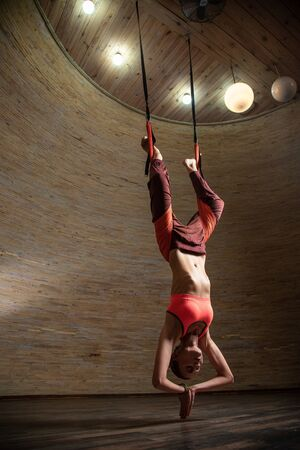 Full length of woman hanging on the aerial yoga straps Banco de Imagens