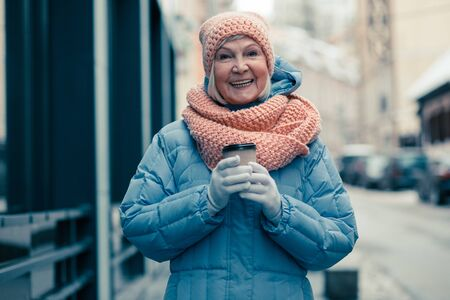 Excited woman smiling while being in the street with carton cup of coffee