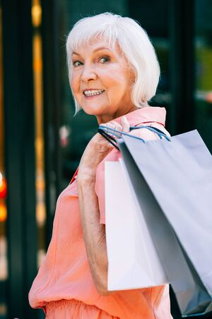 Gladsome aged woman with shopping bags in hand