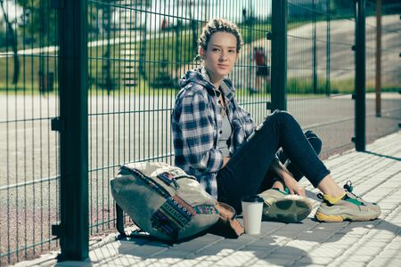 Young woman sitting near the chain link fence with her big backpack