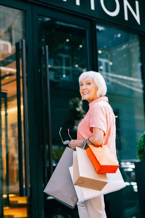Happy pensioner entering clothes shop and smiling
