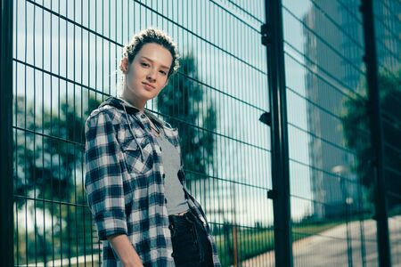 Young lady looking confident while standing next to the chain link fence Reklamní fotografie