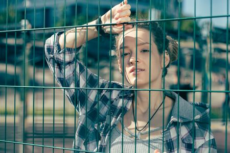 Portrait of thoughtful young lady standing near the chain link fence