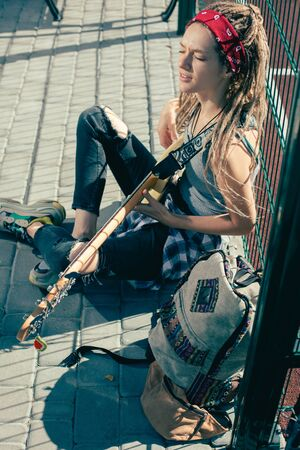 Talented lady singing and playing the guitar outdoors Reklamní fotografie