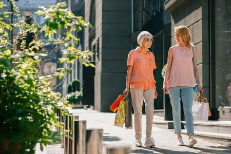 Happy women returning from shop with paper bags in hands Reklamní fotografie