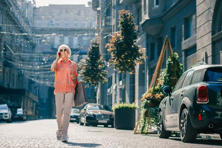 Elderly lady walking and talking on the phone