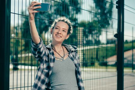 Pretty lady smiling while taking selfies near the chain link fence Reklamní fotografie