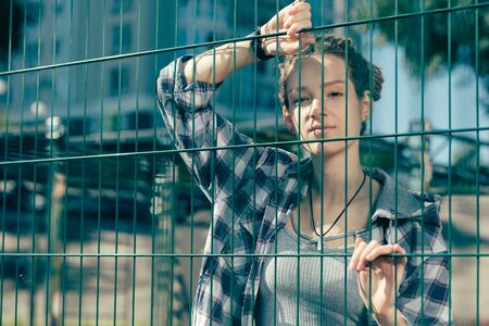 Calm lady looking confident while touching the chain link fence
