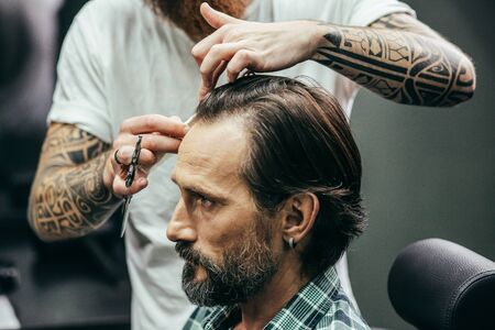 Bearded man frowning and barber combing his hair