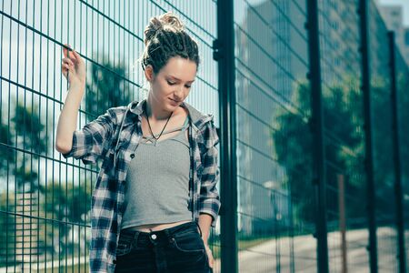 Calm young lady looking down when standing near the chain link fence