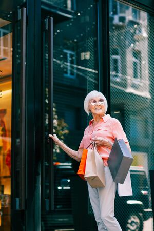 Gladsome elderly woman entering clothes shop with paper bags