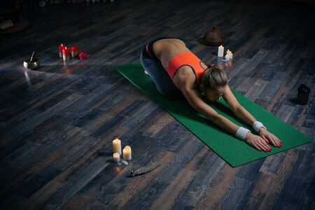 Slim young woman stretching her arms on the yoga mat Banco de Imagens
